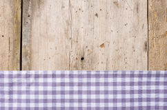 Violet checkered tablecloth on a  wooden background Royalty Free Stock Image