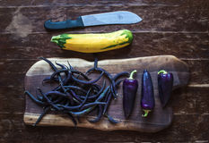 Violet chili peppers, beans and yellow zucchini on Royalty Free Stock Images