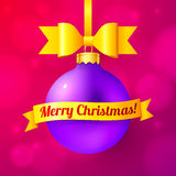 Violet Christmas ball with yellow ribbon and sign Royalty Free Stock Photo