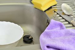 Violet Cleaning cloth and Yellow Sponge. White bowl in a kitchen sink with violet cleaning cloth, yellow sponge and silverware, close up, full frame royalty free stock photos