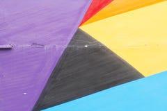 Violet coloré, rouge, jaune mur noir et par bleu peint avec des fissures Image libre de droits