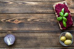 Violet color hummus with basil leaves, olives and onion on brown wooden table, space for text, copy space stock photo