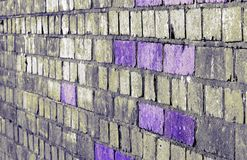 Violet coloured bricks brighten an old railway bridge. An old derelict railway bridge gets a makeover with a splash of purple stock photography