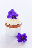 Violet cupcake. Cupcake decorated with whipped cream and violet flowers, selective focus Royalty Free Stock Image