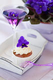 Violet cupcake and cocktail. Cupcake decorated with whipped cream and violet flowers and cocktail, selective focus Royalty Free Stock Image
