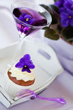 Violet cupcake and cocktail. Cupcake decorated with whipped cream and violet flowers and cocktail, selective focus Stock Images