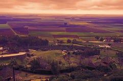 Violet en groen toonlandschap met gebieden en dorp stock afbeeldingen