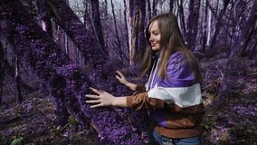Violet fairytale forest. Beautiful happy girl strokes a tree trunk covered with thick, purple moss on a sunny day in a. Violet fairytale forest. A beautiful stock footage