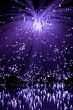 Violet fibre optics. Violet coloured fibre optic light strands cascading against a black background and reflecting into the foreground stock photo