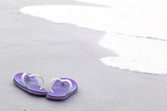 Violet flip-flops on the beach Royalty Free Stock Photography