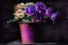 Violet floral still life. Roses bouquet inside violet metal vase still life grunge composition Stock Photography