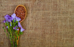 Violet flower of flax and seeds in a wooden spoon on an old brow Stock Photo