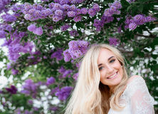 Violet flowers of lilac hang over the smiling blonde lady Stock Photography