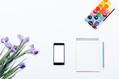 Violet flowers, mobile phone, notebook, pencil and watercolor pa Stock Image