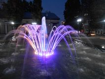 Violet fountain in the town in the night. Stock Photography
