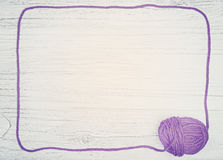 Violet frame made of yarn on wooden board. Stock Photos