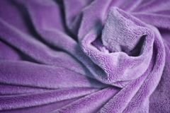 Violet furry fleece fabric Blanket with a lot of folds relief. And color gradient royalty free stock images