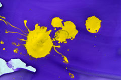 Violet gouache paint and a yellow blotch in the middle. Close-up. Abstract background purple and yellow liquid paint. Artistry, art, creativity Stock Photo