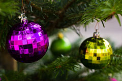 Violet and green glass balls on Christmas tree. Stock Photo
