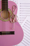Violet guitar for children with treble clef on music sheets back. Ground Royalty Free Stock Image