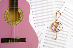 Violet guitar for children with treble clef on music sheets back. Ground Royalty Free Stock Photos