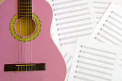 Violet guitar for children with treble clef on music sheets back. Ground Stock Photo