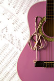 Violet guitar for children with treble clef on music sheets back. Ground for music school Royalty Free Stock Images