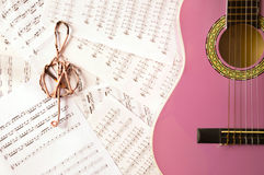 Violet guitar for children with treble clef. On music sheets background for music school Stock Photo