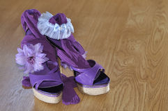 Violet heels with flower and garter. On wooden floor Stock Photos