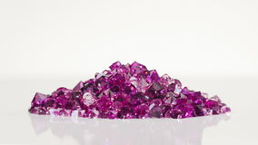 Violet jewel stones heap turning over white background stock video