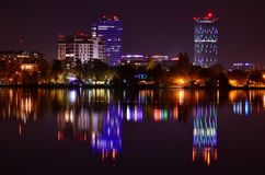 Bucharest night scene with colorful reflection. Night scene with modern building covered in violet and blue lights reflected in lake water surface. Bucharest stock photography