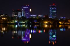 Violet Lights Night Scene With Full Moon And Water Reflection Stock Images