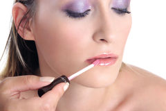 Violet look-step4-lip gloss. Young woman, close up, applying lip gloss Royalty Free Stock Image