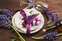 Violet lupins and tableware on the wooden table Stock Image
