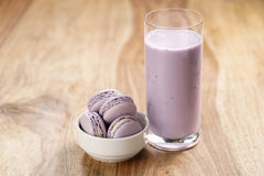 Violet macarons in white bowl with blueberry yogurt on wooden table. Closeup royalty free stock photo