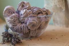 Violet marshmallow in a bowl with lavender flowers. Violet marshmallow in a large glass bowl with lavender flowers in front, stays on a wooden table and Royalty Free Stock Photography