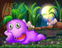 A violet monster resting under the tree in the middle of the nig Royalty Free Stock Image