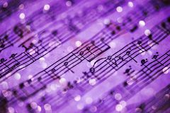 Violet music notes. Music notes sheet in violet tonality and blurred lights background royalty free stock image