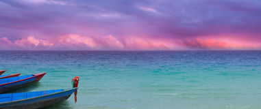 Violet oceon sky with parrot. Exotic ocean panorama with a colorful cloudscape and boats with a parrot in similar, harmonic colors Stock Photos
