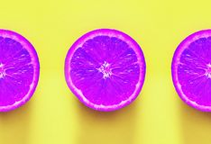Violet oranges. Fruits on yellow background. Surrealism. Violet oranges on yellow background. Surrealism Royalty Free Stock Image