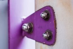Violet painted metal sheets fastened with bolts and stainless nu. Ts. It is some rust stock photography