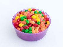 Violet plastic round medium size bowl for loose products filled with colored small-sized sweets isolated on a white background royalty free stock photos