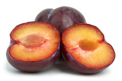 Violet plums: whole and two halves Royalty Free Stock Image