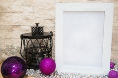 Violet and purple Christmas balls, black lantern, mock up. Violet and purple Christmas balls, black lantern, and white frame mock up. Silver glass beads stock photo