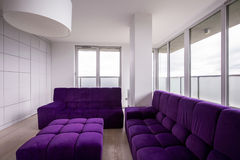 Violet quilted sofa. In modern sitting room Royalty Free Stock Images