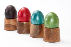 Violet, red, blue and green easter eggs in wooden holder Stock Photography