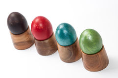 Violet, red, blue and green easter eggs in wooden holder Stock Photos