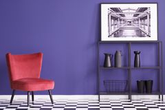 Violet and red flat interior. Black vases on shelves near red suede chair on checkerboard floor in violet flat interior with poster Royalty Free Stock Photo