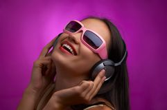 Violet rhythm. Glamour portrait of young brunette in pink sunglasses listening music Stock Image