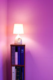 Violet room. Violet theme room detail with a small bookcase, lamp and copyspace Stock Photo
